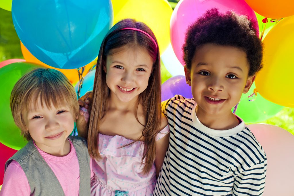 A photo of three children with colourful balloons in the background.